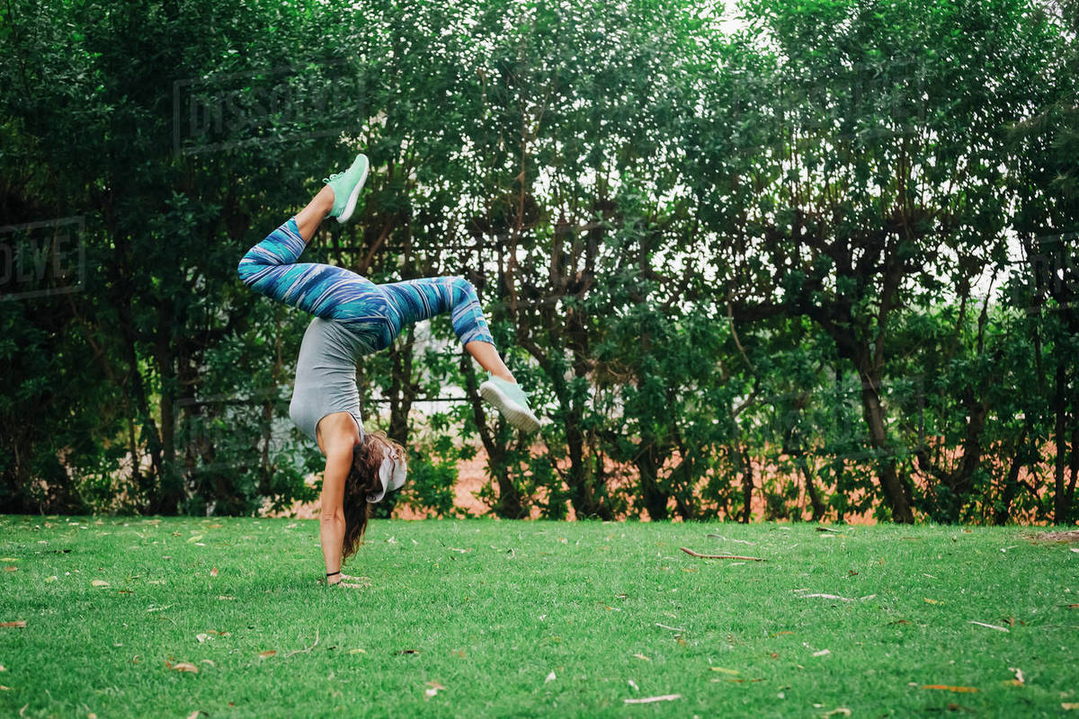 Fit, carefree female personal trainer doing handstand in park Royalty-free stock photo