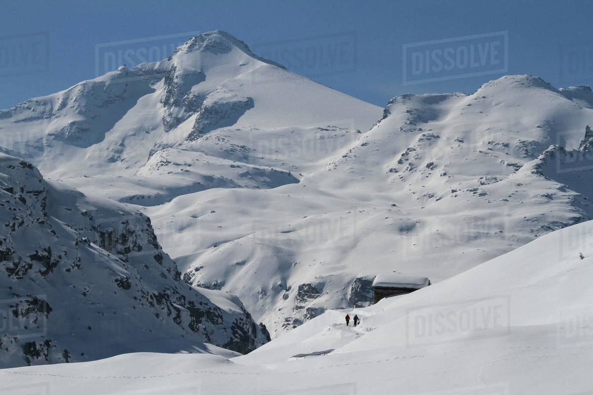 People walking toward cabin on remote, snow covered mountain, Vals, Canton of Grisons, Switzerland Royalty-free stock photo