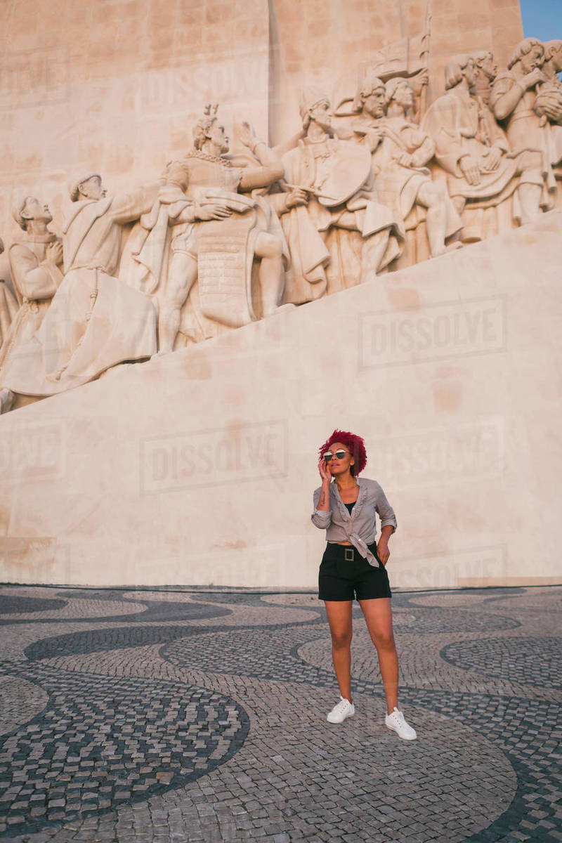 Stylish woman in sunglasses below Monument to the Discoveries, Lisbon, Portugal Royalty-free stock photo