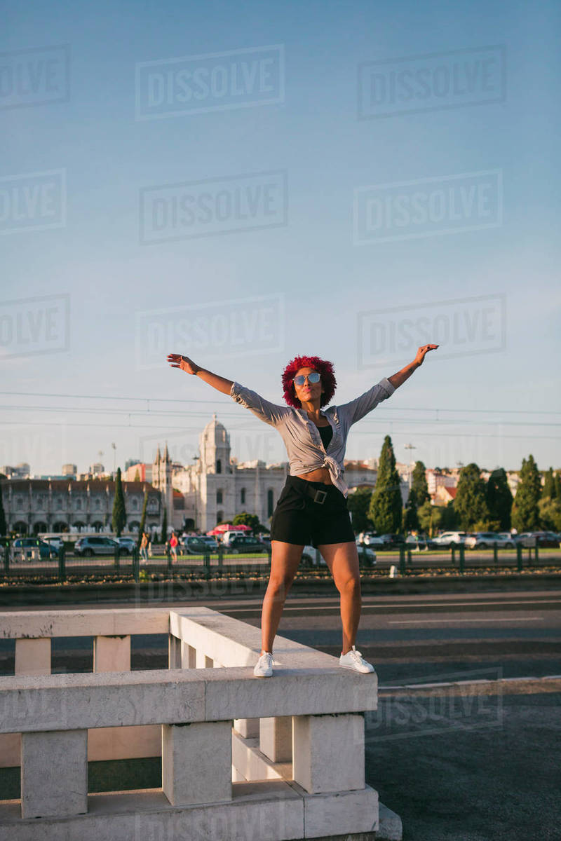 Portrait confident, carefree woman on building ledge with Jeronimos Monastery in background, Lisbon Royalty-free stock photo