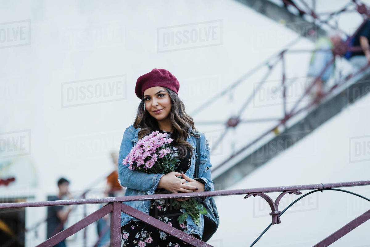 Portrait woman in beret holding flower bouquet Royalty-free stock photo