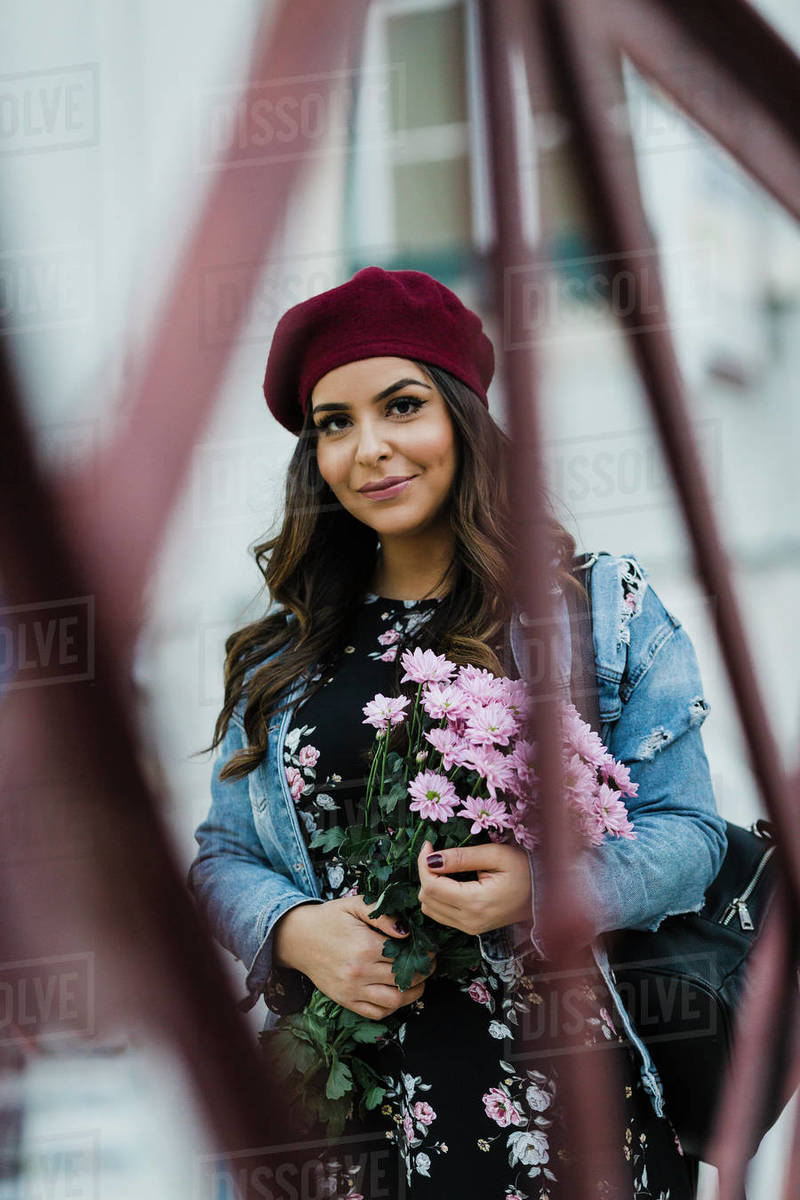 Portrait confident young woman in beret holding flower bouquet Royalty-free stock photo