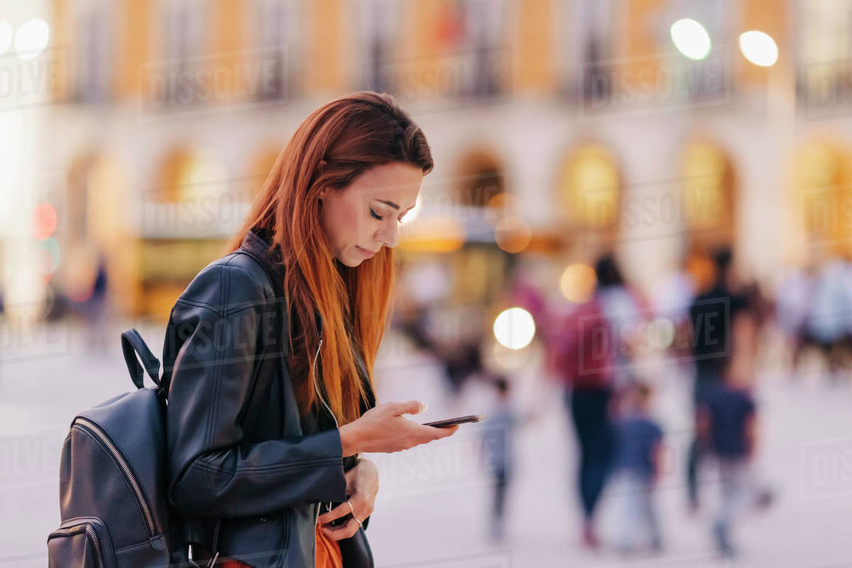 Young woman with backpack using smart phone on urban sidewalk Royalty-free stock photo