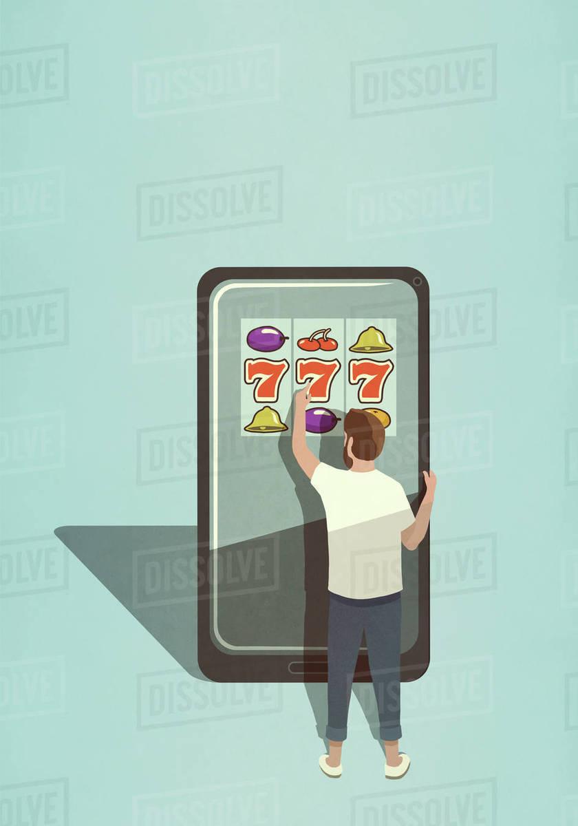 Man playing slot machine game on large smart phone Royalty-free stock photo