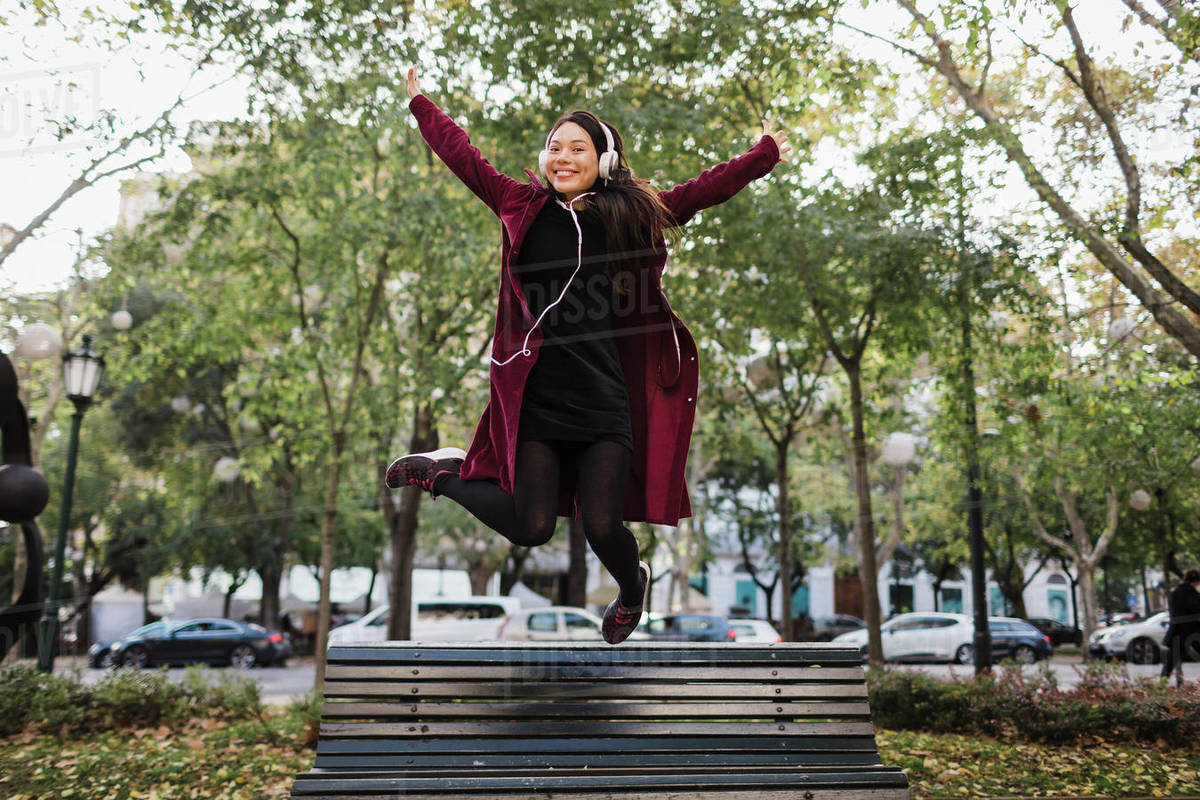 Portrait playful exuberant woman jumping off urban city bench Royalty-free stock photo