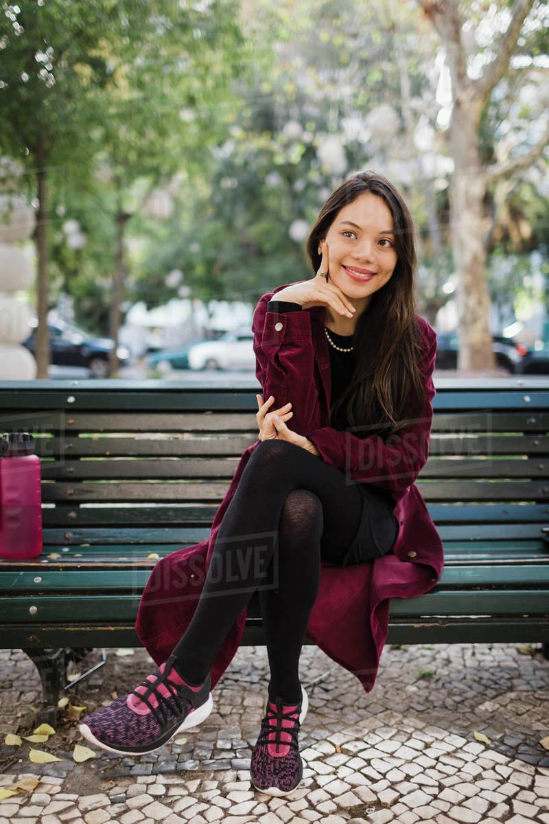 Portrait smiling, stylish woman on park bench Royalty-free stock photo