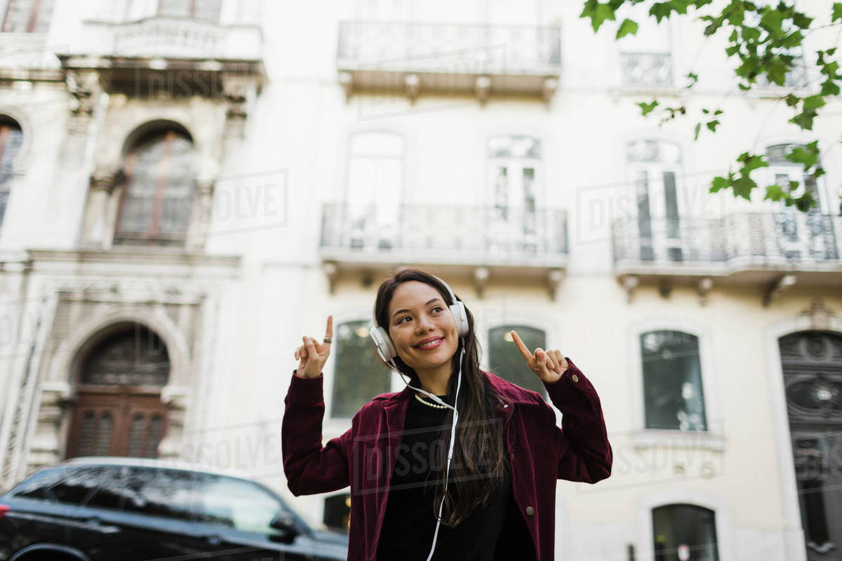 Portrait playful, cool woman listening to music with headphones on urban street Royalty-free stock photo