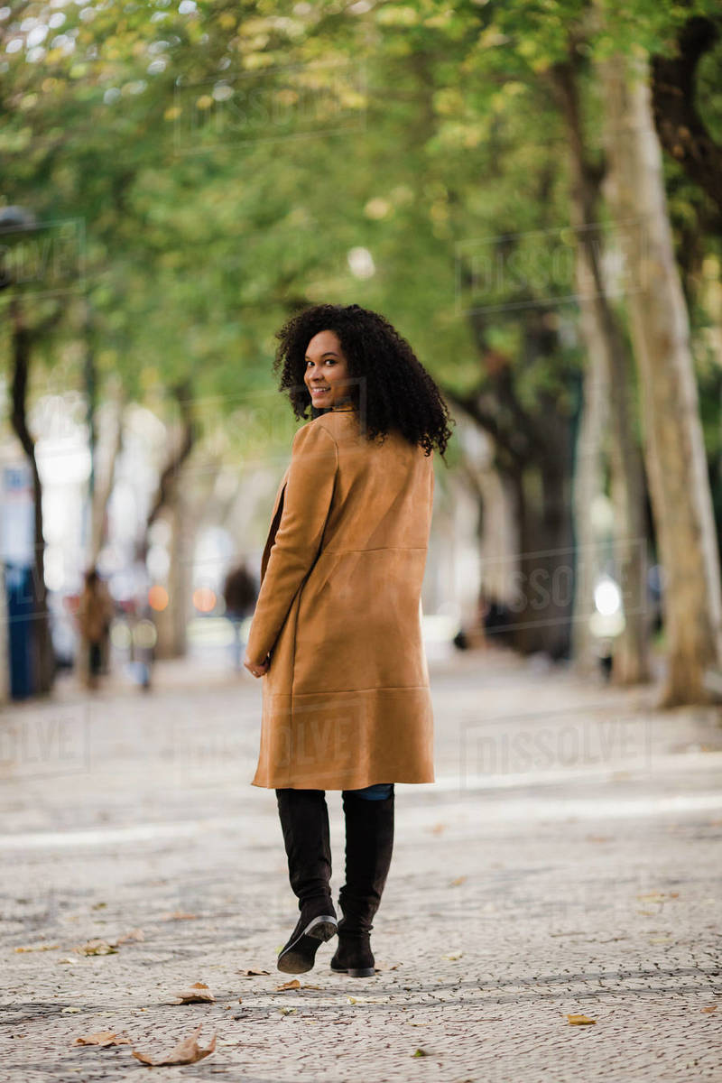 Portrait confident young woman looking over shoulder on treelined sidewalk Royalty-free stock photo