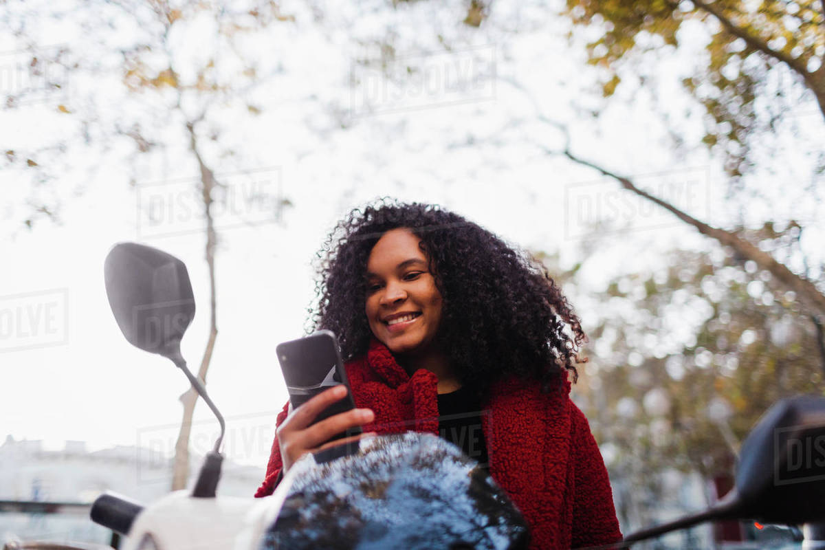Smiling young woman using smart phone on motor scooter Royalty-free stock photo