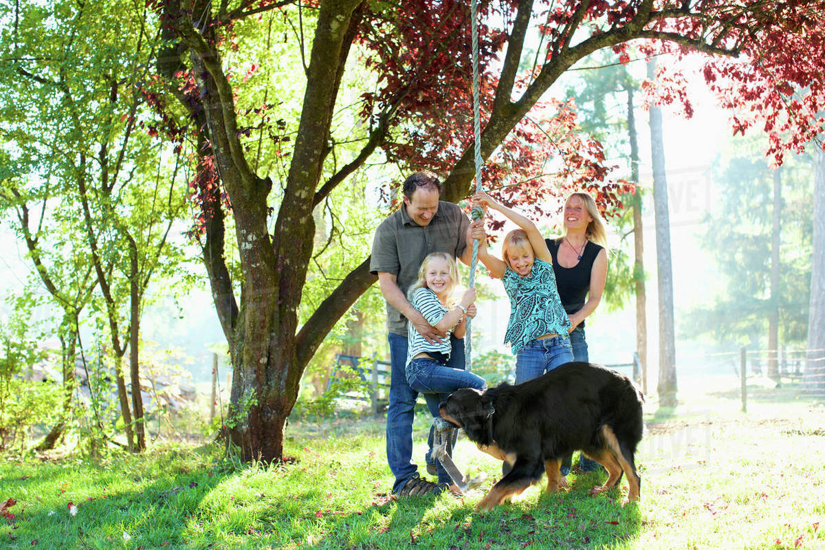 Happy family with dog playing on rope swing in sunny autumn park Royalty-free stock photo