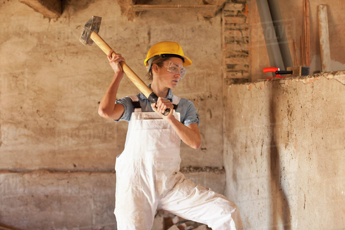 A female construction worker swinging a sledgehammer - Stock Photo ...