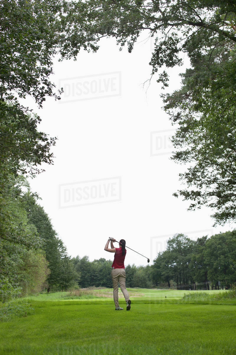 A female golfer teeing off, rear view Royalty-free stock photo