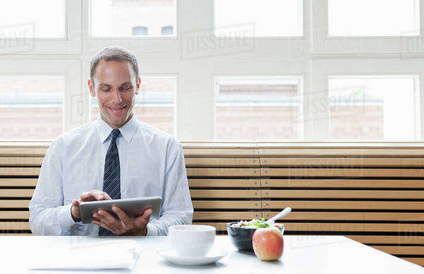 A businessman using a digital tablet on his lunch break Royalty-free stock photo