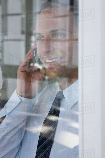 A businessman talking on a mobile phone, viewed through window Royalty-free stock photo